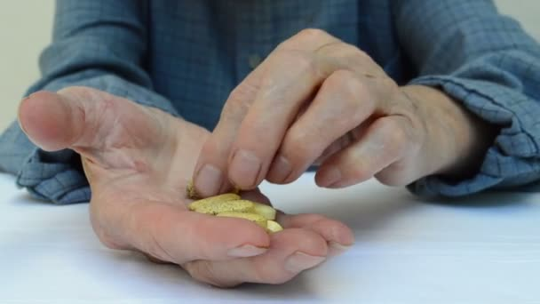 Senior adult holding a medicine pill in his hands. Sort drugs