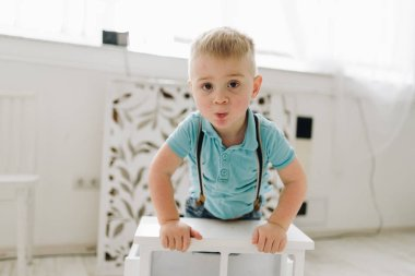 A handsome little boy wearing blue T-shirt and pushing up