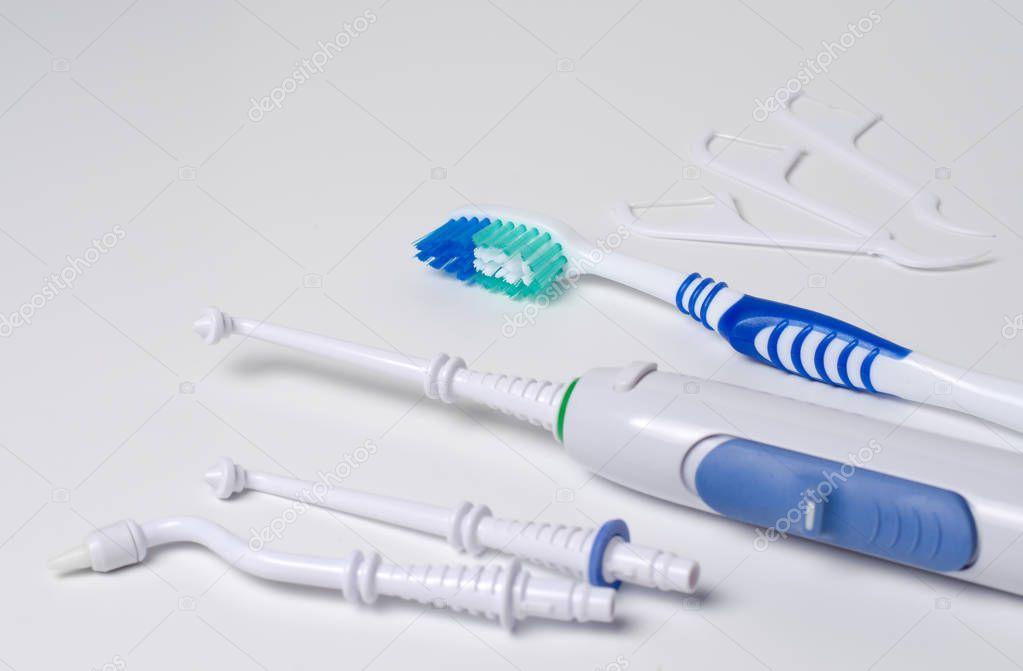 Dental oral irrigator, toothbrush, dental floss. On a white back