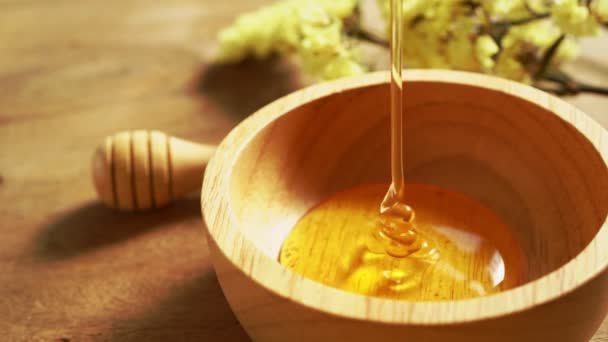 4k makro záběry, Honey nalévání med v dřevěné míse. Detailní záběr. Zdravý organický hustý med namáčení z medové lžíce.
