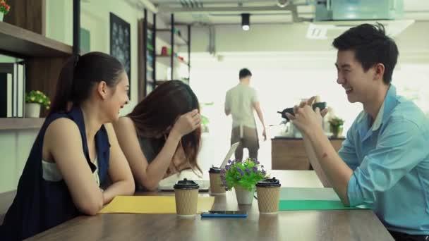Dolgozó fiatal ázsiaiak beszélgetnek és nevetnek egy kávézóban.
