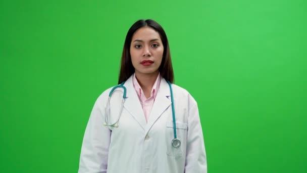 Junge asiatische Ärztin steht mit verschränkten Armen auf dem Green Screen Hintergrund