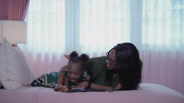 African-American mother teaches her daughter to write in a pink room in bed.