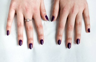 A woman holds her hands steady over white paper towel in a beauty salon as her new purple nail polish dries.
