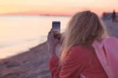 Frau Reisenden mit Smartphone und nehmen Foto von bunten Meer Sonnenuntergang