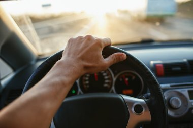 Selective focus mans hand on steering wheel, driving a car at sunset. Travel background