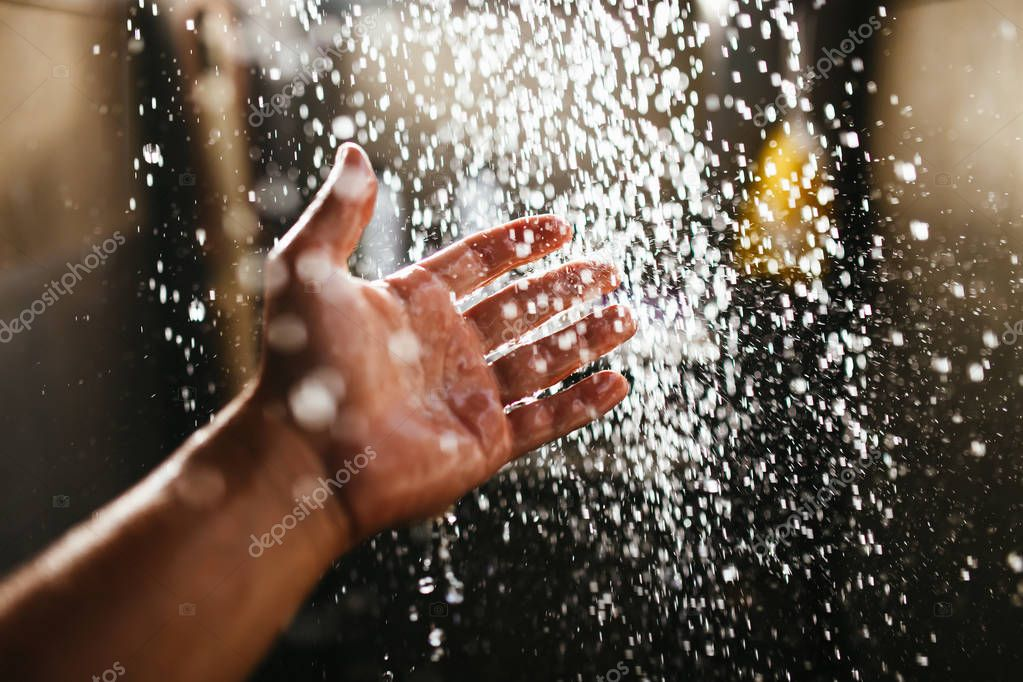 A mans hand in a spray of water in the sunlight against a dark background. Water as a symbol of purity and life