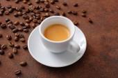 Espresso fehér kerámia csésze kávébab, barna háttér