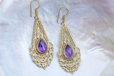 Brass metal earrings with mineral amethyste gemstone on pearl background