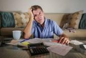 mladá atraktivní strach a zdůraznil muž doma výpočet měsíční daňové výdaje s platbami účetní Kalkulačka dělají banky papírování stres při pohledu zoufalé utrpení finanční problém