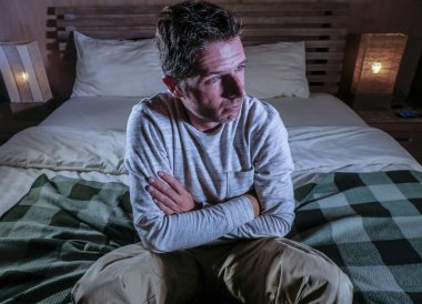 indoors portrait of young desperate and depressed man at home bedroom sitting on bed sad and confused suffering pain and depression crying lost feeling sick in mental health and depression