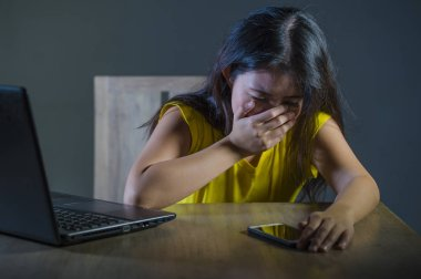 dramatic portrait scared and stressed Asian Korean teen girl or young woman with laptop computer and mobile phone suffering cyber bullying stalked and harassed with internet password hacked
