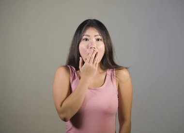 young pretty and amazed Asian Korean girl astonished and shocked in wonder and surprise gesturing with hands covering mouth isolated background in astonishment and stupor face expression