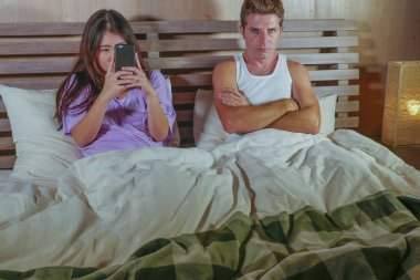 young attractive mixed ethnicity Asian and Caucasian couple in bed with social media addict girlfriend using internet mobile phone ignoring frustrated and upset man moody in relationship problem