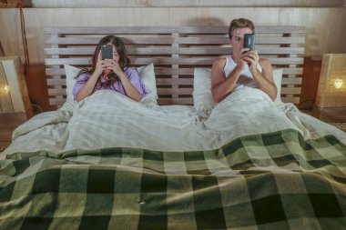 young internet addict couple on bed ignoring and neglecting each other using social media app on mobile phone flirting and on line dating in relationship problem and conflict at home bedroom