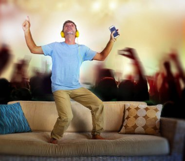 young happy and excited man jumping on sofa couch listening to music with mobile phone and headphones singing and dancing crazy imagine as famous rock band concert and fans audience