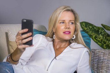 beautiful and happy blond woman early 40s relaxed at home living room using internet social media app on mobile phone smiling lying comfortable on sofa couch in lifestyle concept
