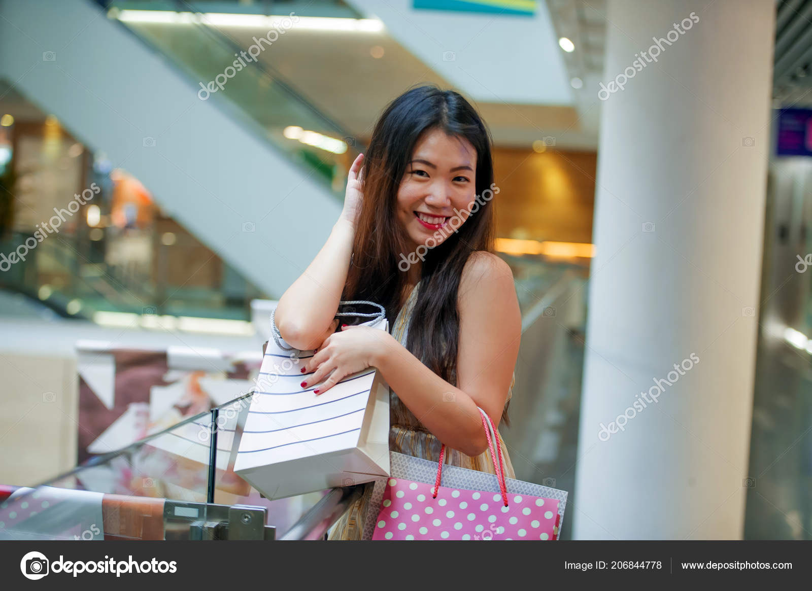 db7dabeec17 Lifestyle indoors portrait of young happy and beautiful Asian Korean woman  carrying shopping bags in mall buying cheerful walking around fashion store  ...
