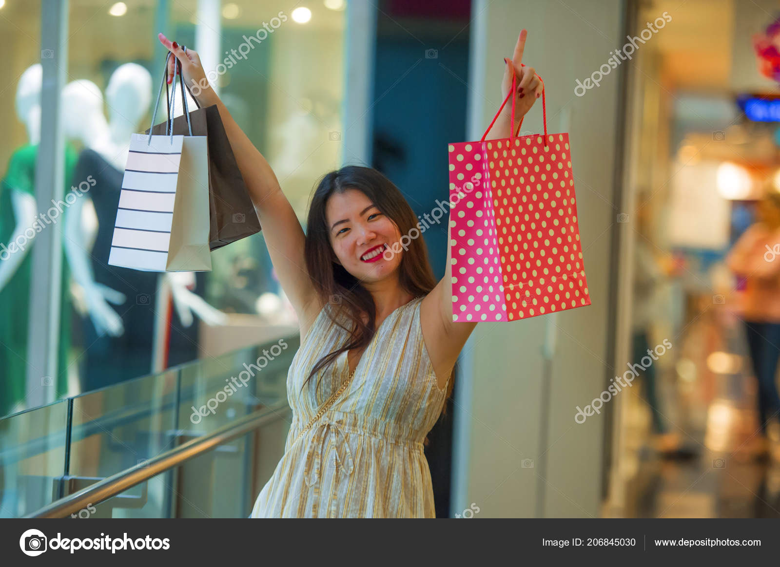6acbce35e7c Lifestyle indoors portrait of young happy and beautiful Asian Korean woman  carrying shopping bags in mall buying cheerful walking around looking  fashion ...