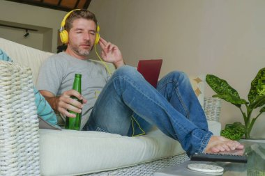 lifestyle indoors portrait of young happy relaxed and attractive man sitting at home sofa couch with headset and laptop listening to internet music online enjoying song relaxed drinking beer bottle