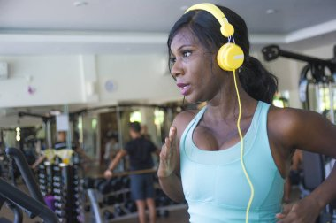 indoors gym portrait of young attractive black afro American woman with headphones training hard all sweaty at fitness club a treadmill running workout in body care and healthy lifestyle concept