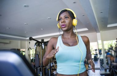 indoors gym portrait of young attractive black afro American woman with headphones training hard a hard treadmill running workout at fitness club in body care and runner healthy lifestyle