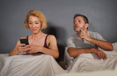 girlfriend or wife using mobile phone in bed and suspicious frustrated husband or boyfriend feeling upset suspecting betrayal and cheating in man woman couple relationship problem concept