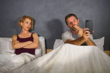 husband or boyfriend using mobile phone in bed and suspicious frustrated wife or girlfriend feeling upset suspecting betrayal and cheating in man woman couple relationship problem concept