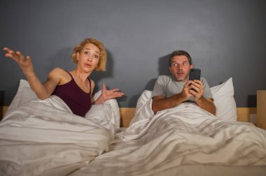 lifestyle portrait of husband or boyfriend using mobile phone in bed with angry frustrated wife or girlfriend , the woman feeling ignored and upset in man internet addiction couple problem
