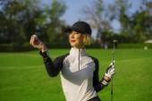 portrét venku životní styl mladých krásná a šťastná žena v golfu drží míč a putter klubu s úsměvem veselá ve stylové golfové oblečení izolované na zeleném pozadí put