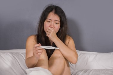 young depressed and desperate Asian Korean woman crying and scared testing positive result on pregnancy test alone in bed feeling remorse and stress in irresponsible mistake concept