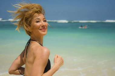 young attractive and happy woman running on tropical paradise beach with white sand and vivid turquoise sea color jogging barefoot and smiling in fitness holidays and healthy lifestyle concept