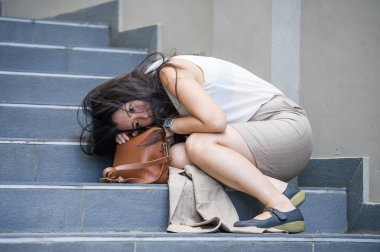 young depressed and desperate Asian Japanese businesswoman crying alone sitting on street staircase suffering stress and depression crisis being victim of mobbing or fired losing her job