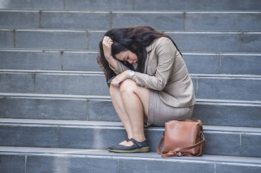 young depressed and desperate Asian Korean business woman crying alone sitting on street staircase suffering stress and depression crisis being victim of mobbing or fired losing her job