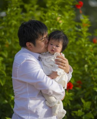 young happy and proud man as father of sweet little baby girl holding her daughter in front of flowers garden at holidays resort enjoying together outdoors in family lifestyle concept