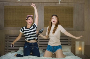 young happy and excited Asian Chinese girls singing together online karaoke song with microphone and mobile phone jumping at home on bed as girlfriends having fun and women friendship concept