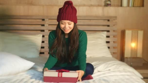 šťastná a krásná Asijská americká dívka v zimní čepice drží Vánoce prezentovat krabice s mašlí s úsměvem nadšený a veselá, sedí doma postel slavit Vánoce obdrží dárek