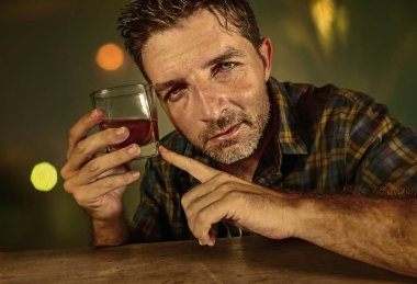 young sad and depressed alcoholic man with whiskey glass wasted and drunk failing resisting to drink in bar pub at night falling into alcohol abuse in addiction and alcoholism problem