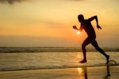 sziluettjét a fiatal, vonzó illik sportos és erős fekete afrikai amerikai férfi futás-on sunset beach képzési kemény és futásnak a tengervíz profi atléta és futó edzés