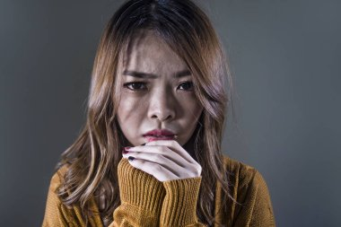 young crazy desperate and sad Asian Korean woman looking depressed and helpless feeling anguish and pain on isolated dark background in pain face expression suffering depression