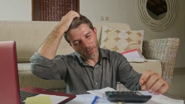 mladí zdůraznil a strach člověka doma obývacího pokoje pomocí kalkulačky a notebook dělá domácí účetnictví papírování pocit ohromen peníze daňových výdajů a finanční stav