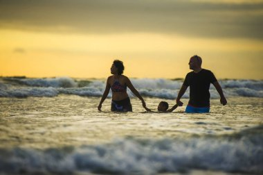 lifestyle silhouette of couple and little son walking relaxed on sunset beach enjoying romantic Summer holidays family trip the parents holding the child playing happy with sea waves