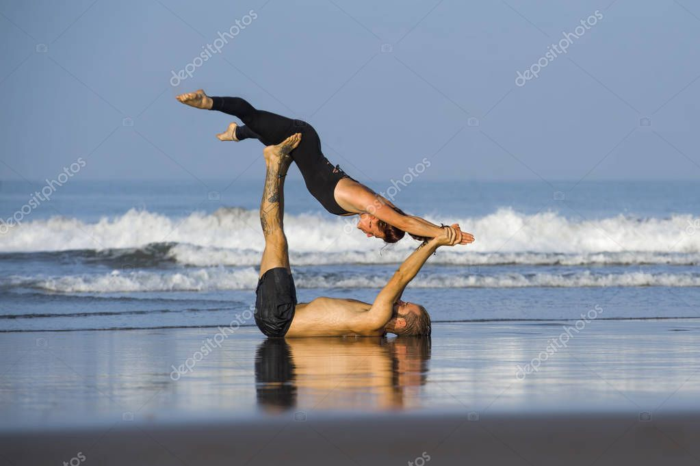 young attractive and beautiful acrobat couple practicing acroyoga exercise concentrated keeping balance practiing yoga on the beach in relaxation and meditation concept
