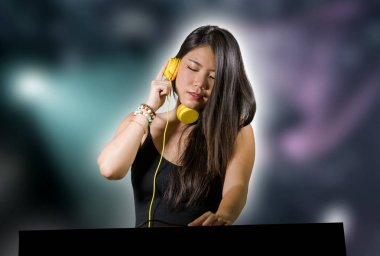 young beautiful and attractive Asian Japanese DJ woman remixing music at night club wearing headphones in clubbing party and deejay  lifestyle concept isolated background