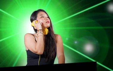young beautiful and attractive Asian Korean DJ woman remixing music at night club wearing headphones isolated on flashes and laser lights background in clubbing party concept