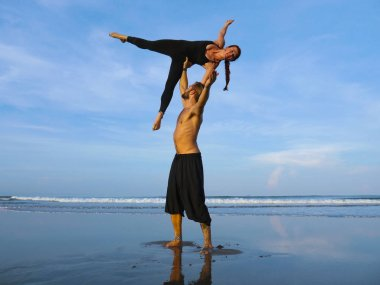 healthy and attractive fit couple of acrobats  doing acroyoga balance and meditation exercise on beautiful desert beach practicing balance and harmony posing