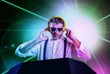 young attractive and cool DJ in shirt and suspenders remixing music at night club using headphones in party strobo and laser lights background in clubbing and nightlife