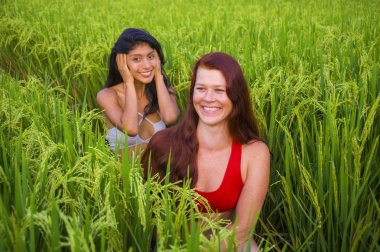 young beautiful latin woman and her attractive red hair girlfriend both girls enjoying Summer holidays together walking on rice field smiling happy relaxed in diversity ethnicity