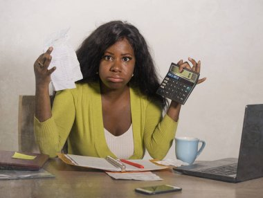 young stressed and overwhelmed black African American woman doing domestic accounting with calculator feeling upset and angry holding paperwork in financial stress