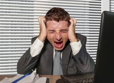 young stressed and overwhelmed businessman in suit and necktie desperate working at office laptop computer desk screaming crazy suffering stress problem